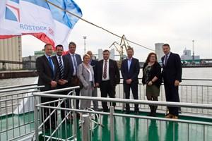 Die Geschäftsführer von Rostock Port, Rostocks Hafenkapitän und Vertreter der Reedereien Finnlines, Scandlines, Stena Line, transfennica und TT-Line vor der Kulisse des Rostocker Überseehafens.
