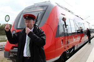 Infrastrukturminister Christian Pegel gibt den Abfahrtsbefehl für den ersten S-Bahn-Zug nach den Bauarbeiten in Richtung Warnemünde, Lokführer Jens Labuzinski freut sich, dass die Strecke wieder frei ist