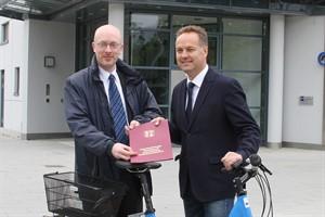 Infrastrukturminister Christian Pegel (links) übergibt Bau- und Umweltsenator Holger Matthäus einen Förderbescheid für die Potenzialanalyse zu den Rostocker Radschnellwegen
