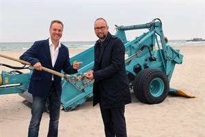 Umweltsenator Holger Matthäus (links) und Tourismusdirektor Matthias Fromm zeigen, was die neue Strandreinigungsmaschine aus dem Sand filtert