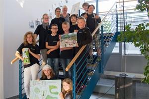 Kinder der Ecolea-Schule präsentieren mit Lehrerin Nicole Jahn (links oben) ihre Freizeitideen für Warnemünde: Verkehrsgarten, Büchersäule, Abenteuerspielplatz und Wissenslehrpfad (von unten nach oben)