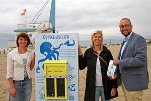 Nardine Stybel, Kristin Plühmer und Matthias Fromm präsentieren den neuen Ostsee-Ascher am Strand von Warnemünde (v.l.n.r.)