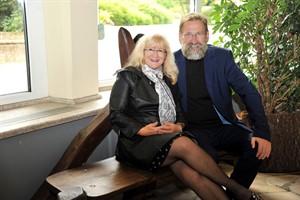 """Lotto-MV-Geschäftsführerin Barbara Becker und Zoodirektor Udo Nagel testen die """"Patenschaftsholzbank"""" im Haus der Zwergflusspferde (Foto: Joachim Kloock)"""