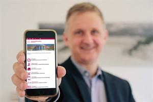 Prof. Dr. Christian Schmidt, Ärztlicher Vorstand der Universitätsmedizin Rostock, zeigt die neue App auf seinem Mobiltelefon (Foto: Unimedizin Rostock)