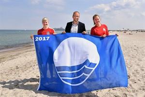 Tourismusdirektor Matthias Fromm und die Rettungsschwimmerinnen Kimberly-Sophie Stein (r.) und Alina Tristram (li.) von der DRK-Wasserwacht präsentieren die Blaue Flagge 2017 (Foto: Joachim Kloock/TZRW)