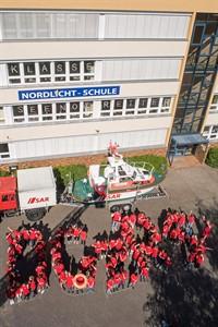 Vor dem Boddenbootgespann der Freiwilligen-Station Wustrow bilden Mädchen und Jungen der Nordlicht-Schule die Buchstaben DGzRS, die Abkürzung für die Deutsche Gesellschaft zur Rettung Schiffbrüchiger (Foto: DGzRS/Frank Hormann)
