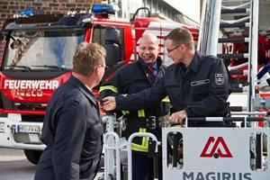 Senator Chris Müller-von Wrycz Rekowski übergibt ein neues Drehleiterfahrzeug an die Feuerwehr und macht gleich eine Testfahrt mit der Leiter.
