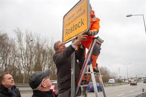 Rostocks Verkehrssenator Holger Matthäus und Oberbürgermeister Roland Methling beobachten, wie Rektor Prof. Schareck dabei hilft, das erste neue Ortseingangsschild mit dem Namenszusatz Hanse- und Universitätsstadt anzubringen.
