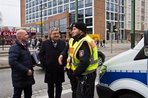 Caffier im Gespräch mit Polizeikräften auf dem Rostocker Weihnachtsmarkt