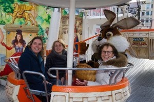 Der Osterhase testet mit Inga Knospe von der Großmarkt GmbH, Jasmina Kohler von Unicef und Marlies Urbigkeit das Riesenrad auf dem Rostocker Ostermarkt.