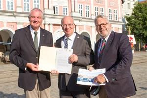 Oberbürgermeister Roland Methling (Mitte) übergibt die Bewerbung für die BUGA 2025 an Helmut Selders und Jochen Sandner von der DBG
