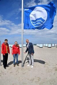 Die DRK-Rettungsschwimmer Max Cornelius und Sarah Wenzel hissen gemeinsam mit Matthias Fromm, Tourismusdirektor von Rostock & Warnemünde, die Blaue Flagge am Strand von Warnemünde (Foto: TZRW/Joachim Kloock)