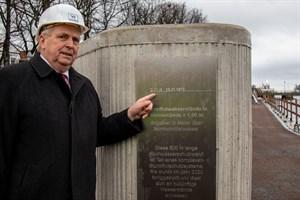 Umweltminister Dr. Till Backhaus zeigt den 1872 gemessenen höchsten Wasserstand an der neuen Sturmflutschutzwand in Warnemünde
