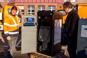 René Weilandt zeigt Umweltsenator Holger Mattäus das Innenleben. Unten befindet sich eine normale 120-Liter-Tonne. (Foto: Archiv)