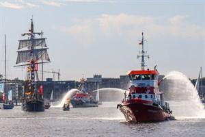 """Begleitet durch Feuerlöschboot und Seenotkreuzer wurde die """"Santa Barbara Anna"""" aus ihrem Winterlagen in den Stadthafen Rostock verholt"""