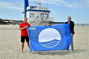 Eike Reck, Rettungsschwimmer der DRK Wasserwacht, und Matthias Fromm, Tourismusdirektor Rostock & Warnemünde, präsentieren die Blaue Flagge 2020 (Foto: TZRW/Joachim Kloock)