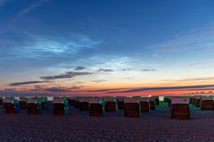 Leuchtende Nachtwolken über dem Strand von Rostock-Warnemünde