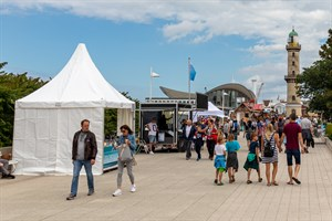 An 27 Ständen bieten Händler auf der Warnemünder Sommerpromenade ausgewählte Ware von Schmuck über Kunsthandwerk bis hin zu Sommerartikeln