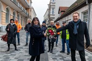 Bausenator Holger Matthäus übergibt Anliegerin Ines Heinrich einen Blumenstrauß zur Sanierung der Georginenstraße in Warnemünde