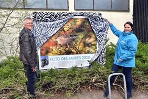 Das Siegerfoto 2020 ist enthüllt und am Zwergflusspferdhaus zu finden, hier mit Zookuratorin Antje Angeli und Preisträger Lothar (Foto: Zoo Rostock/Joachim Kloock)
