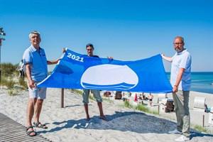Die Blaue Flagge weht wieder in Markgrafenheide und Warnemünde - Henry Klützke (Ortsbeiratsvorsitzender Markgrafenheide), Manuel Brumme (Wachtdienstkoordinator DRK Wasserwacht) und Tourismusdirektor Matthias Fromm (Foto: Julia Junge/DRK)